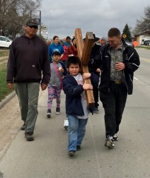 Little Danny Gangone carries the cross.