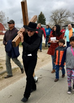 Fr. Bill O'Brien, SJ, carries the cross.
