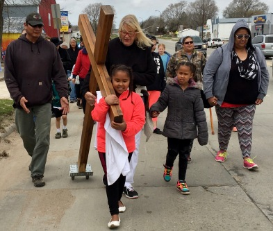 Nancy Moore with one of her students carrying the cross.