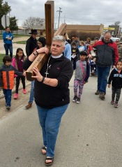 The Rev. Dr. Lauren R. Stanley carries the cross.